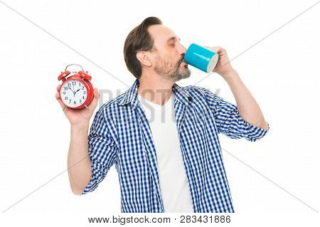 Waking Up Refreshed And Energized. Bearded Mature Man Drinking Coffee With Clock In Hand. Mature Man