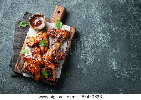 Roasted Chicken Wings In Barbecue Sauce With Sesame Seeds And Parsley On A Wooden Board On A Concret