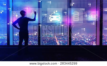 Ev With Man Writing On Large Windows High Above A Sprawling City At Night