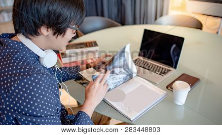 Young Asian Guy University Student Reading Book While Working With Laptop Computer In Library. Self