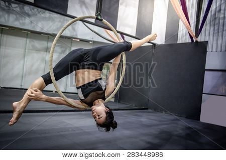 Asian Gymnast Girl Doing Her Gymnastics Performance On Aerial Hoop Or Aerial Ring In Fitness Gym.