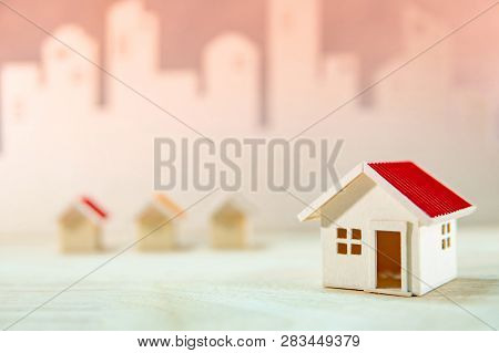 Real Estate Or Property Investment. Home Design Concept. Wooden House Models On The Table With City