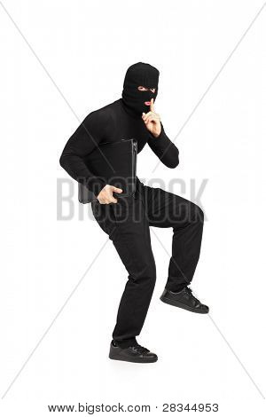 Full length portrait of a man in robbery mask holding a briefcase with finger on the lips gesturing silence isolated on white background