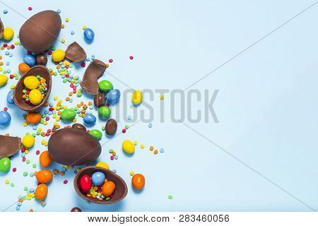 Broken And Whole Chocolate Easter Eggs, Multicolored Sweets On Blue Background. Concept Of Celebrati