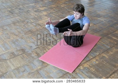A girl in a gray T-shirt on a pink rug raises her legs. Fitness exercise to strengthen the abdominals. Athletic woman training in bodyflex. poster