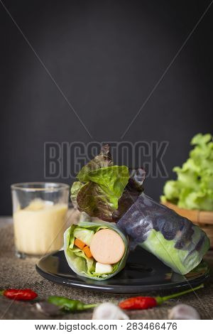 Salad Rolls On Black Plate Placed On A Sack With Chilli And Garlic Placed In Front Of There Is Salad