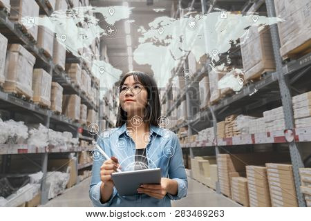 Portrait Of Happy Young Attractive Asian Entrepreneur Woman Looking At Inventory In Warehouse Using
