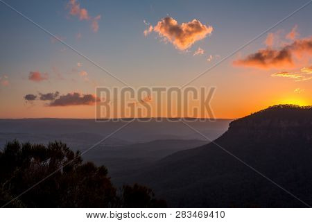 Sunset Behind The Escarpment Cliffs Of The Blue Mountains, Withdrawing Its Light From The Valley Lea