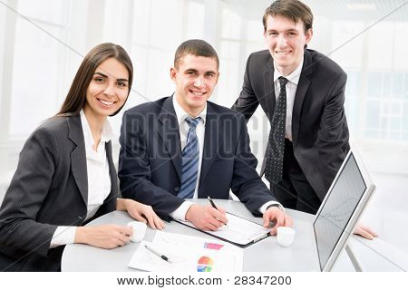Happy business colleagues looking at camera