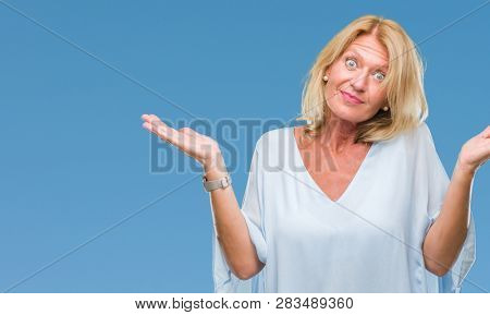 Middle age blonde business woman over isolated background clueless and confused expression with arms and hands raised. Doubt concept.