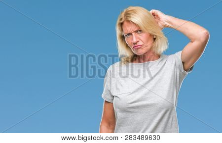 Middle age blonde woman over isolated background confuse and wonder about question. Uncertain with doubt, thinking with hand on head. Pensive concept.