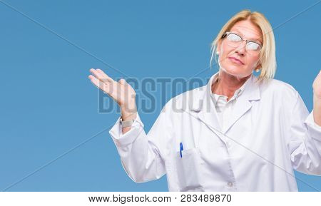 Middle age blonde therapist woman wearing white coat over isolated background clueless and confused expression with arms and hands raised. Doubt concept.