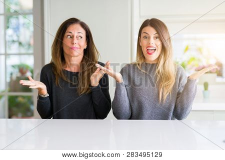 Beautiful family of mother and daughter together at home clueless and confused expression with arms and hands raised. Doubt concept.