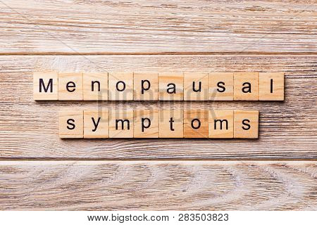 menopausal symptoms word written on wood block. menopausal symptoms text on wooden table for your desing, concept poster