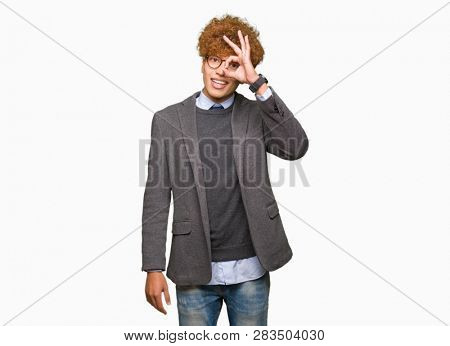 Young handsome business man with afro wearing glasses doing ok gesture with hand smiling, eye looking through fingers with happy face.