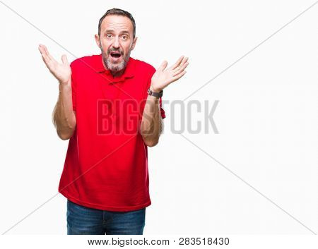Middle age hoary senior man over isolated background clueless and confused expression with arms and hands raised. Doubt concept.