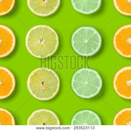 Citrus Fruits pattern on green background. Orange, Lime, Lemon slices background. Flat lay, top view.. Pop art design, creative summer concept.