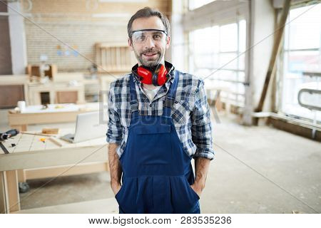 Happy confident middle-aged bearded joiner in protective goggles wearing ear protectors on neck standing in workshop and holding hands in pockets while looking at camera. poster