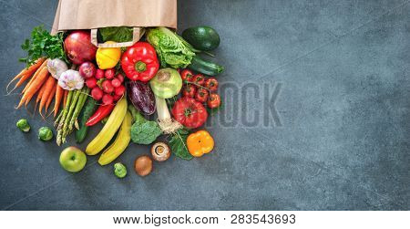 Healthy food selection. Shopping bag full of fresh vegetables and fruits. Flat lay food on table