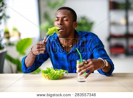 Healthy Eating. Happy Young Black Man Eating Salad In The Morning In Kitchen