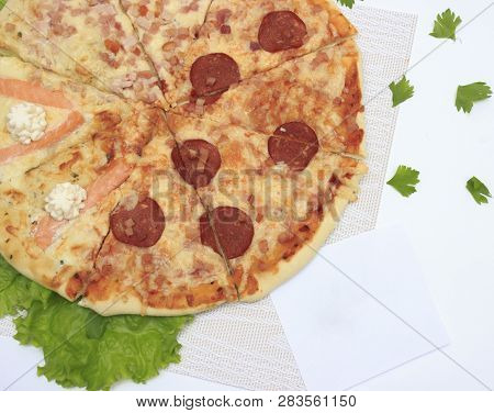 Hot Tasty Homemade Pizza With Sausage, Fish Cheese And Other Ingredients In Cut Form Is Ready To Eat