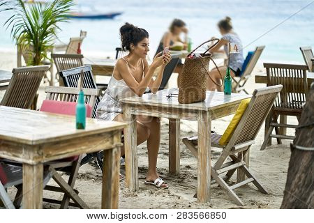 Tanned Woman Using Her Smartphone In Outdoor Restaurant On Tropical Beach