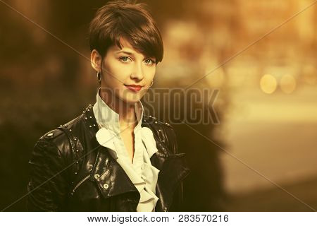 Happy young fashion woman with pixie hair walking on city street Stylish female model wearing black leather jacket and white blouse