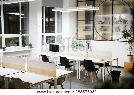 Modern Open Space Office Interior: Black Chairs At Tables In Rows Under Hanging Lamp, Potted Plants