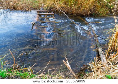Little River In The Autumn. Water Flows In A Small River. Water Flows Through A Wooden Obstacle