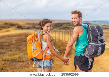 Happy young couple tourists in love holding hands walking on trek hike with backpacks. Hikers on nature travel hiker trail destination smiling happy. Interracial relationship.