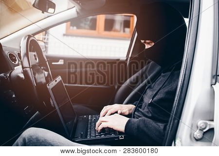 Masked thief hacker in a balaclava disarming car security systems and stealing a car poster