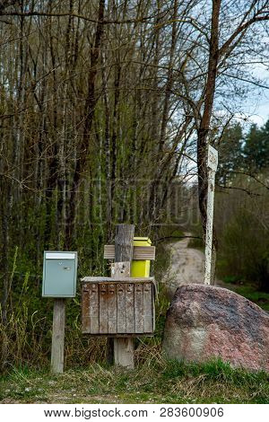 Spring Landscape With Rural Mailbox. Old Mailbox At Rural Roadside Next To The Big Stone In Latvia.