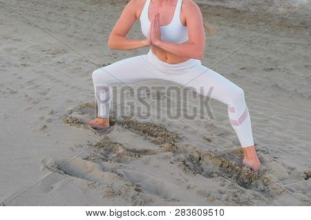Young Woman Doing Yoga Plie Squat On The Sandy Beach At Sunrise.