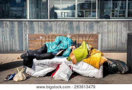 Homeless Man, Poor Homeless Man Or Refugee Sleeping On The Wooden Bench On The Urban Street In The C