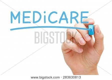 Hand Writing Medicare With Blue Marker On Transparent Wipe Board. United States National Health Insu