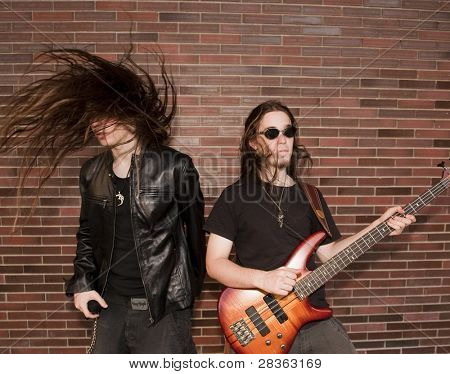 Two joung musician jumping against brick wall