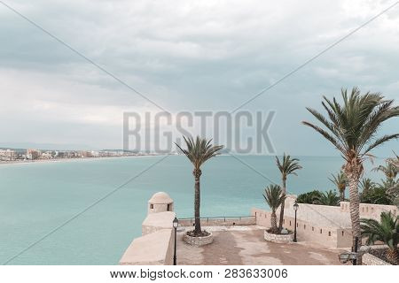 Warm Turquoise Sea And Palm Trees Of Peniscola, The Resort In The Province Of Castellon, Valencian C
