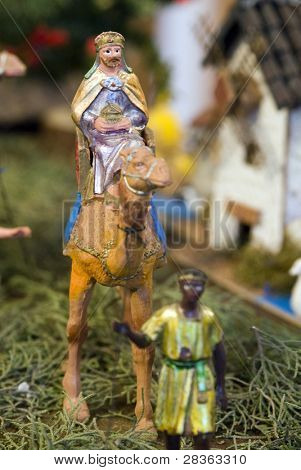 Older wise king with dromedary and page. Focus in wise king figurine.