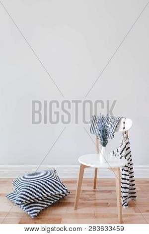 Modern Interior With Stylish Chair, Lavender Flowers, Striped Cushions And Clothes, On Gray Wall Bac