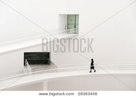 Young business woman walking on modern building