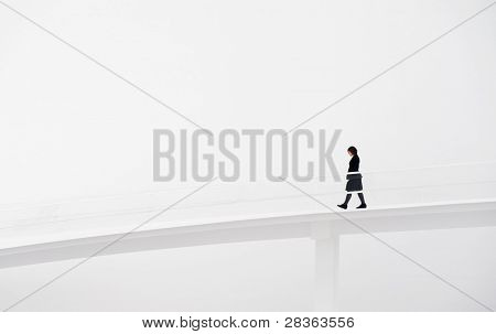 Young woman in black clothes walking in white runway