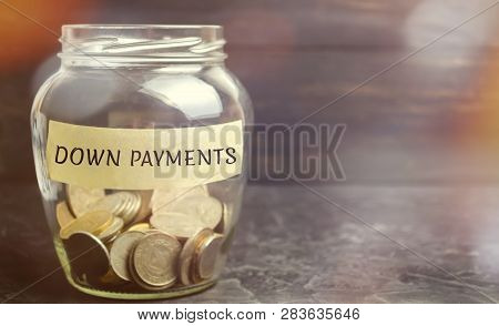 Glass Jar With The Word Down Payments. Payment Used In The Context Of The Purchase Of Expensive Item