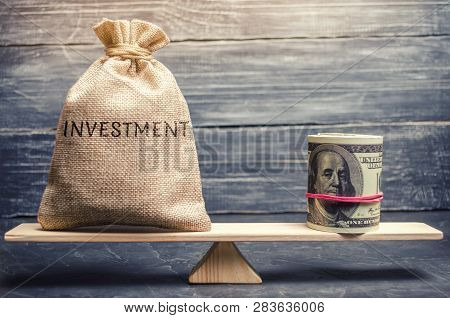 Money Bag With The Word Investments And Dollars On Scales. Attraction Of Financial Resources For Inv