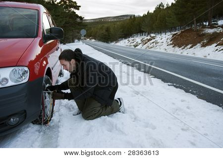 Young handsome man installing snow chain on his car.