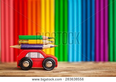Miniature Red Car Carrying A Colorful Pencils On Plasticine Multi-colored Wall. Back To School Conce