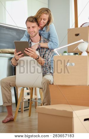 Young Couple Moving In New Home.sitting And Relaxing After Unpacking.looking Something On Laptop. Yo