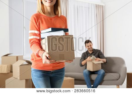 Woman Carrying Box Full Of Books While Man Unpacking Other In New House. Moving Day