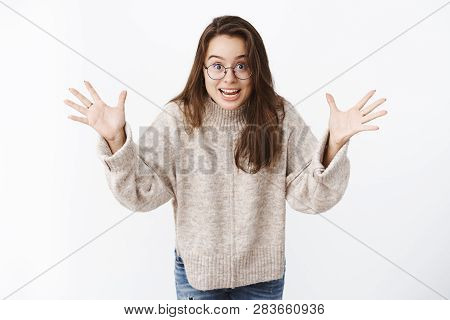 Guess What. Portrait Of Excited Happy Young Surprised Woman In Glasses And Sweater Gesturing With Ra