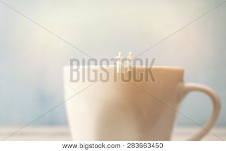 Miniature Couple In Love Sitting On Coffee Cup Edge