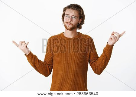 Waist-up Shot Of Hesitant Unsure Boyfriend Standing Thoughtful Smirking And Frowning, Pointing Sidew